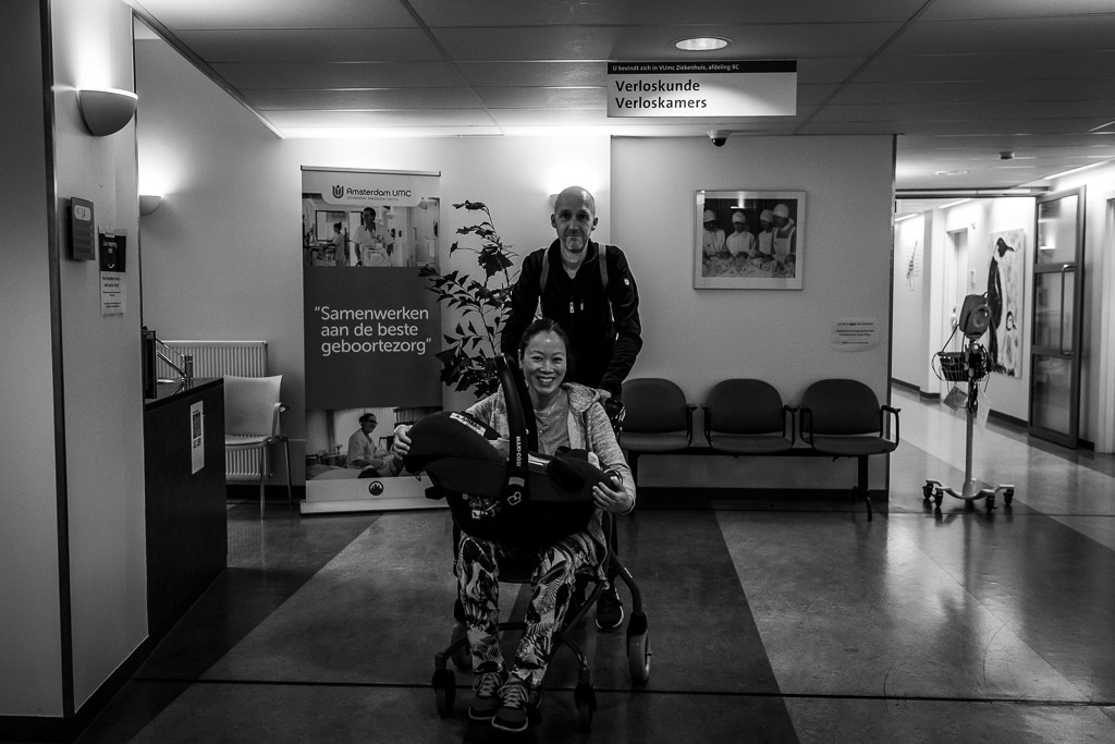 De ouders verlaten met hun pasgeboren baby het ziekenhuis VU in Amsterdam gefotografeerd door Sandrinos Geboortefotografie