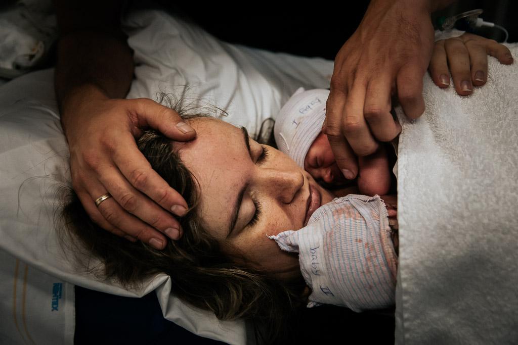 Trotse mama met haar pasgeboren tweeling op haar borst in het ziekenhuis van Leeuwarden gefotografeerd door Sandrinos Geboortefotografie uit Purmerend