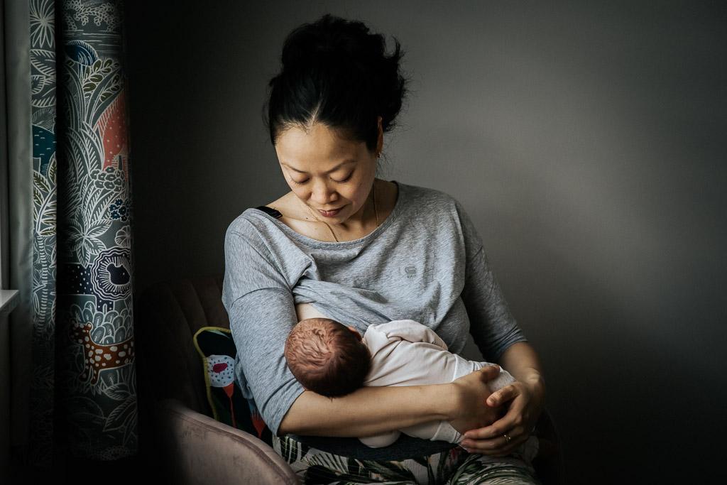 Moeder geeft borstvoeding aan haar pasgeboren dochter gefotografeerd door Sandrinos Fotografie