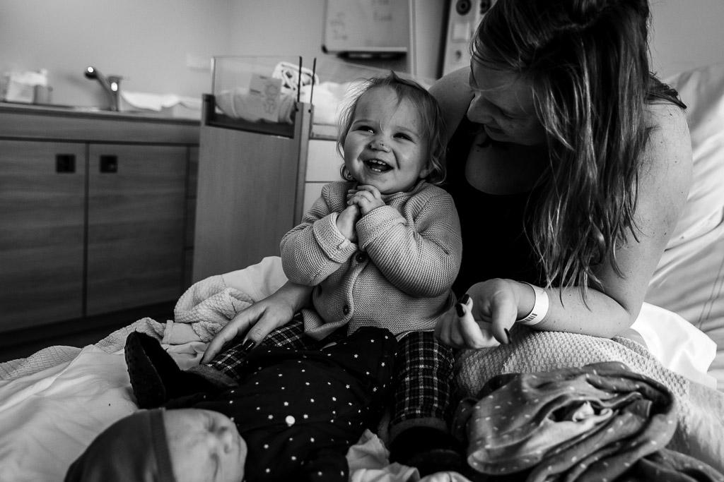 Trotse oudste zus met haar pasgeboren babyzusje