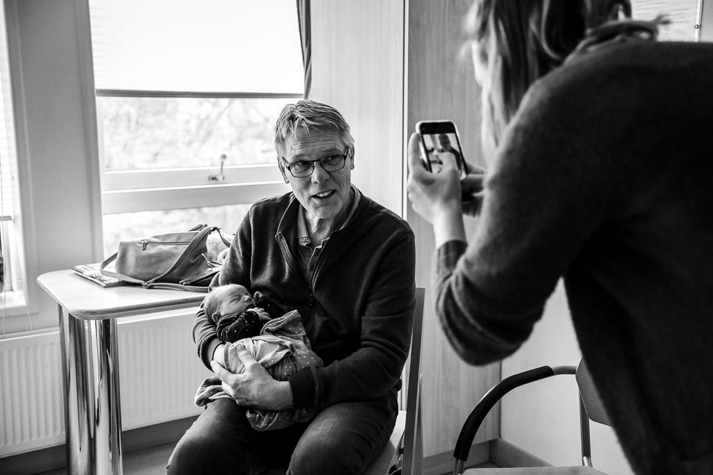 Opa met zijn pasgeboren kleinzoon op de foto