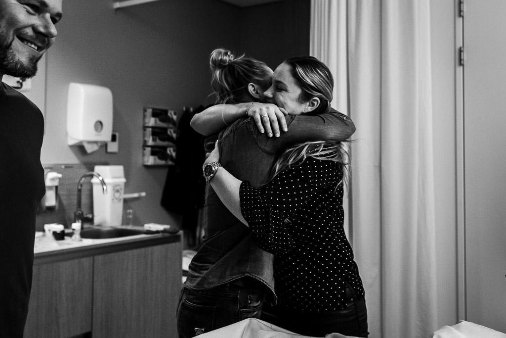 Trotse tantes omhelzen elkaar als ze hun pasgeboren nichtje bewonderen in het ziekenhuis