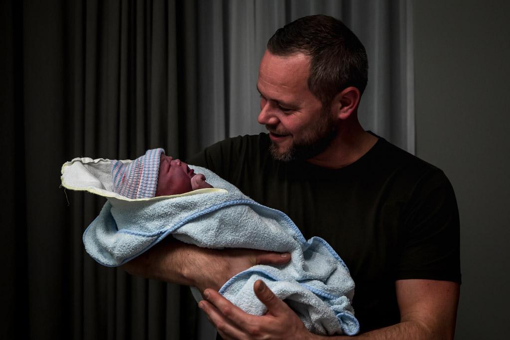 Trotse papa met zijn pasgeboren dochter voor het eerst in zijn armen, dit maakt geboortefotografie zo mooi