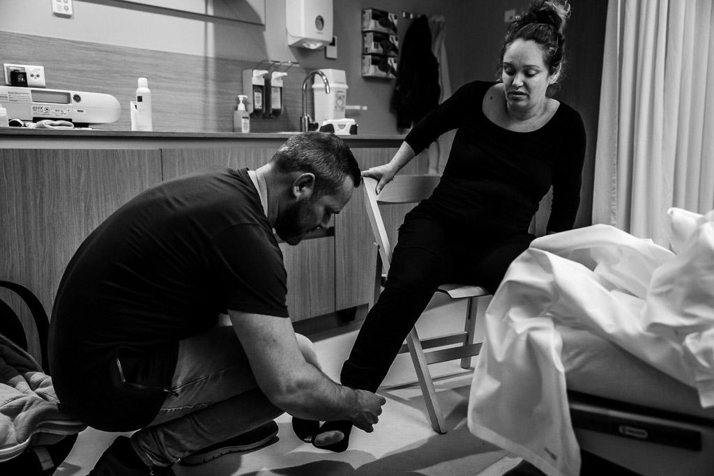 Papa helpt mama na de bevalling met het aantrekken van haar schoenen