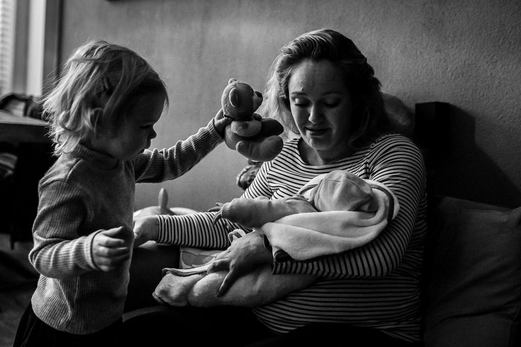 Grote zus geeft haar pasgeboren zusje een kadootje