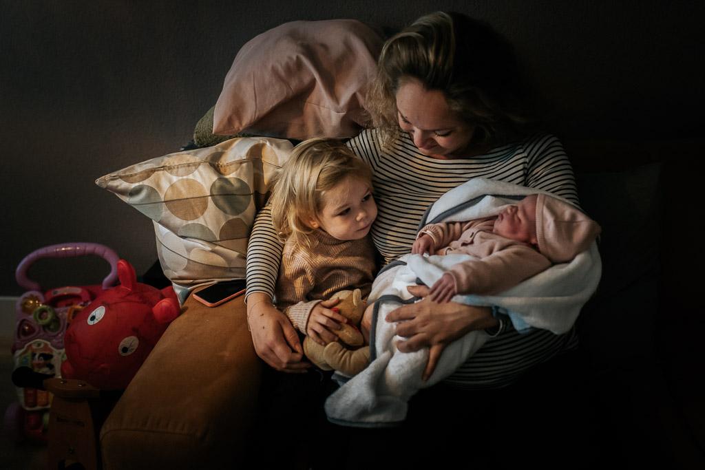 Grote zus ontmoet haar pasgeboren zusje thuis na de bevalling in het ziekenhuis in Zaandam