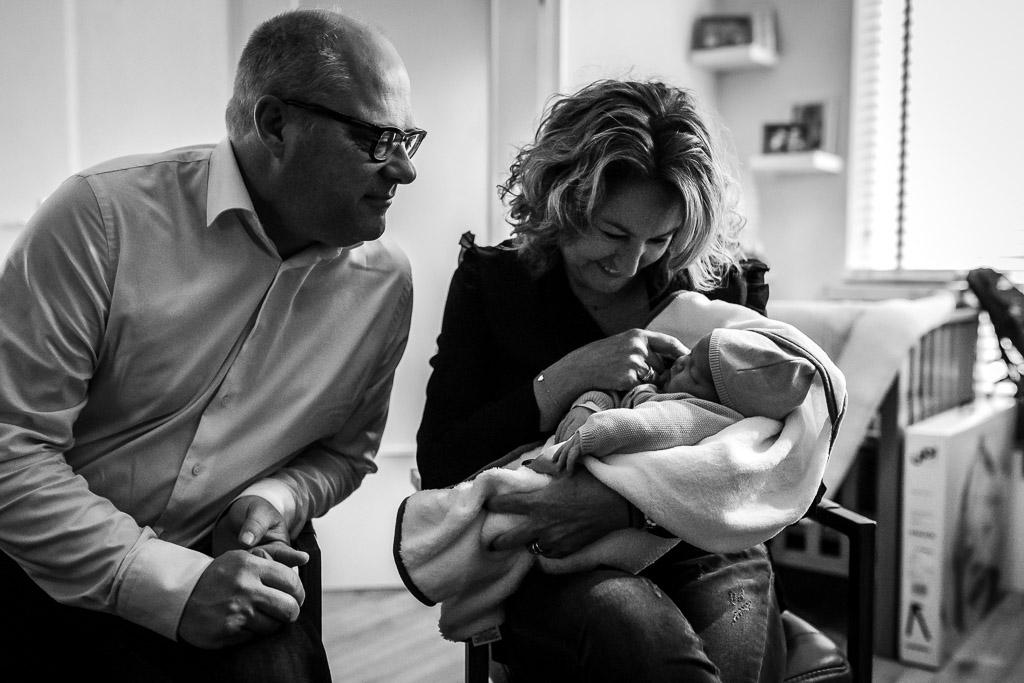 Trotse opa en oma bewonderen hun kleindochter van één jaar oud