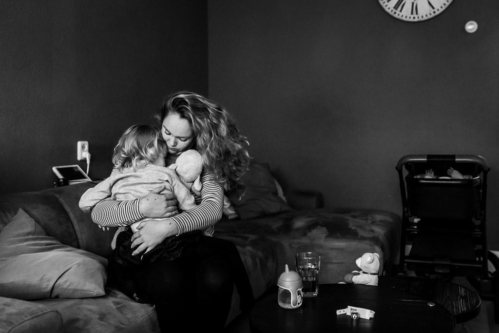 Grote zus knuffelt met haar mama die net uit het ziekenhuis is gekomen na de bevalling