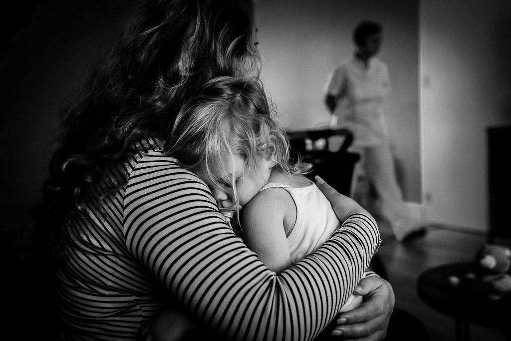 Ziek meisje zoekt troost bij haar moeder die net bevallen is in het ziekenhuis van haar zusje