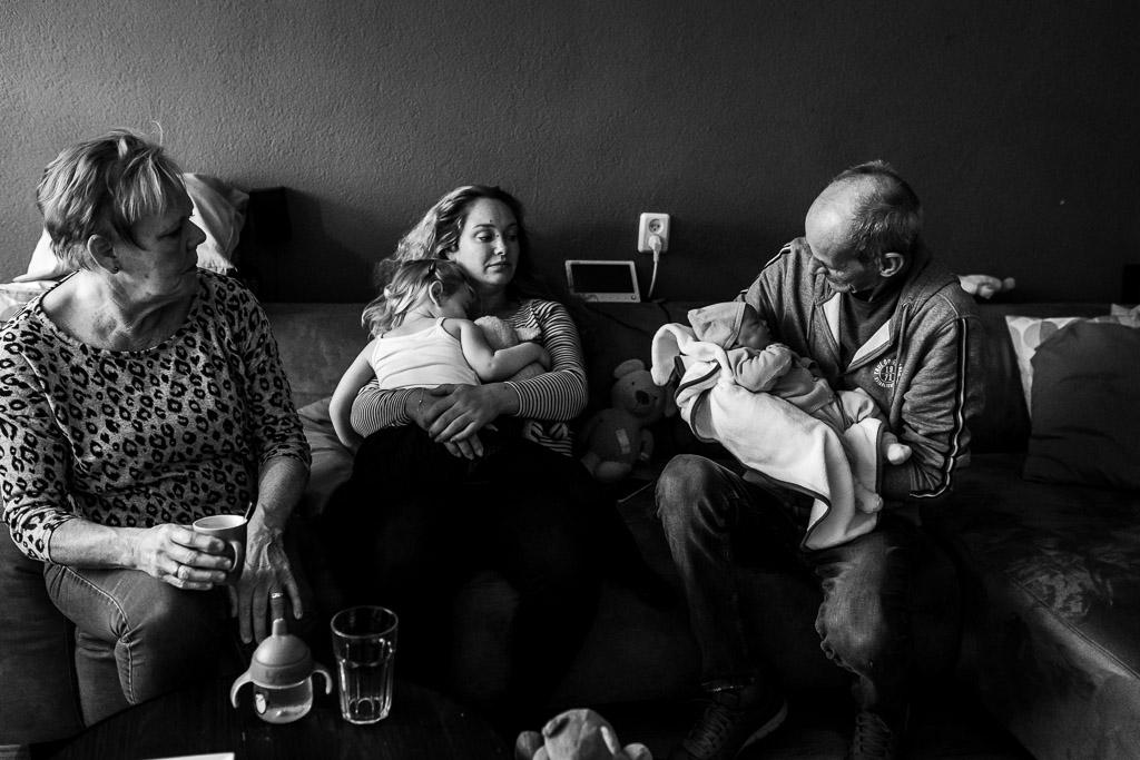 Dit is geboortefotografie, trotse grootouders met hun pasgeboren kleindochter op de foto