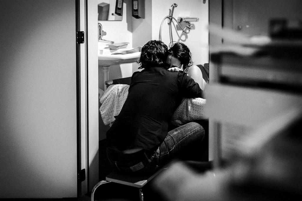 De barende vrouw zoekt steun in het bevalbad vastgelegd door Sandrinos Geboortefotografie